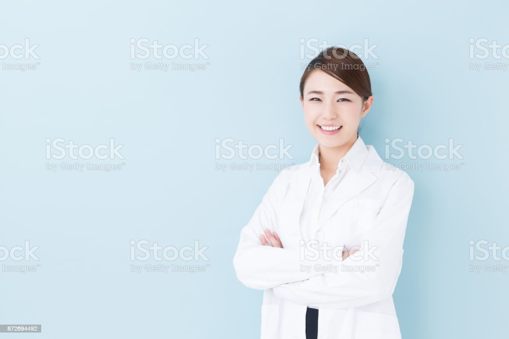 portrait of asian doctor isolated on blue background stock photo