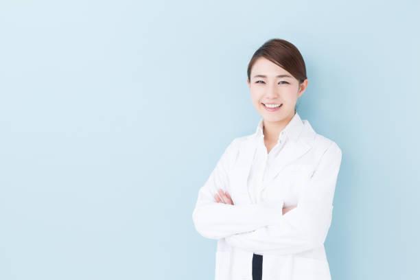 青の背景に分離されたアジア医師の肖像画 - スタジオ 日本人 ストックフォトと画像