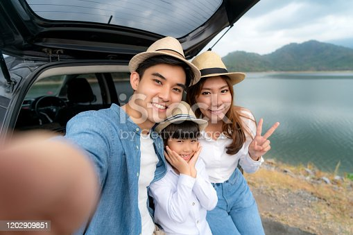 807410214 istock photo Portrait of Asian family sitting in car with father, mother and daughter selfie with lake and mountain view by smrtphone while vacation together in holiday. Happy family time. 1202909851