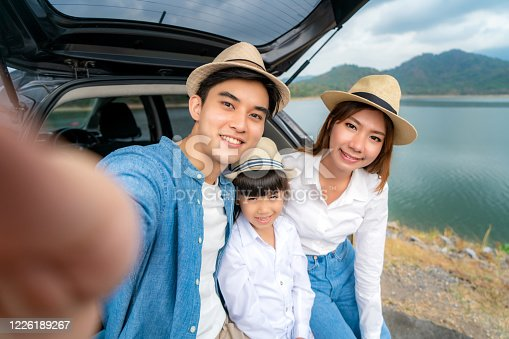 972962180 istock photo Portrait of Asian family sitting in car with father, mother and daughter selfie with lake and mountain view by smrtphone while vacation together in holiday. Happy family time. 1226189267