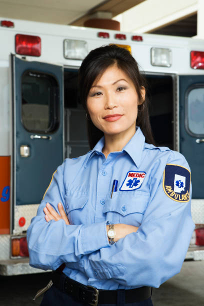 Portrait of Asian female paramedic in front of ambulance Portrait of Asian female paramedic in front of ambulance civil servant stock pictures, royalty-free photos & images