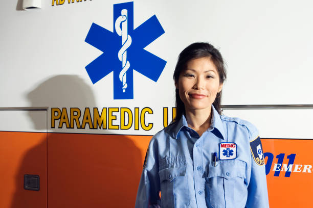 portrait of asian female paramedic next to ambulance - paramedic stock pictures, royalty-free photos & images