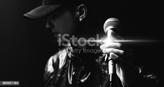 istock portrait of asian handsome singer posing on microphone, black and white 895957484