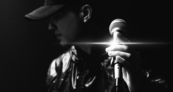 portrait of asian handsome singer posing on microphone, black and white