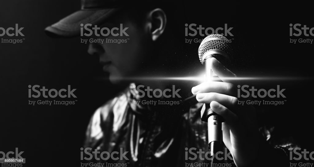 portrait of asian handsome singer posing on microphone, black and white stock photo