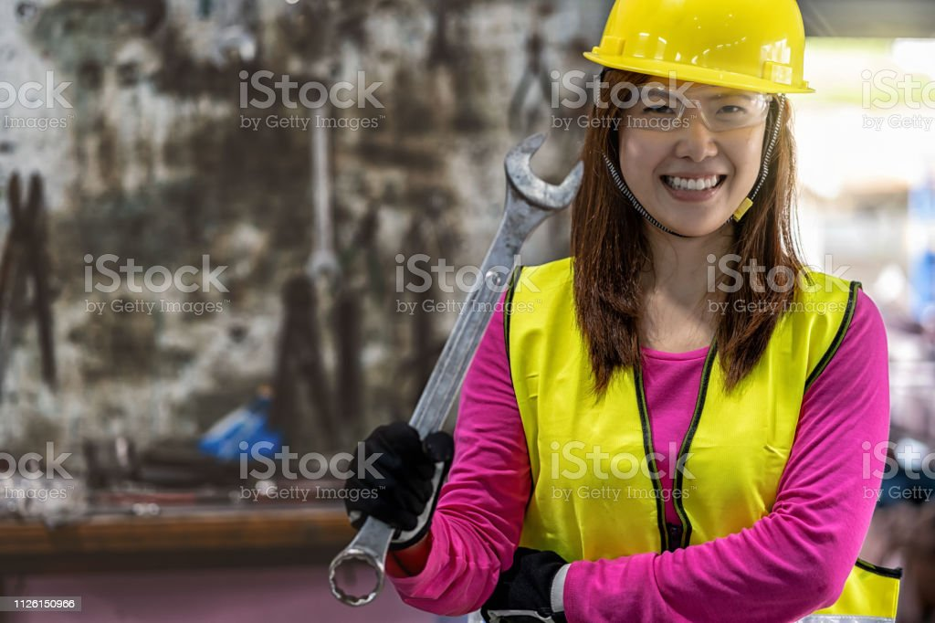 Portrait of Asian machinist in safety suit holding the wrench over...