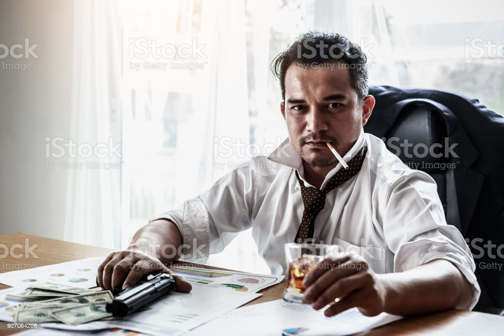 Portrait of Asian mafia gangster with gun and whiskey in hand sitting at table in the safe house stock photo