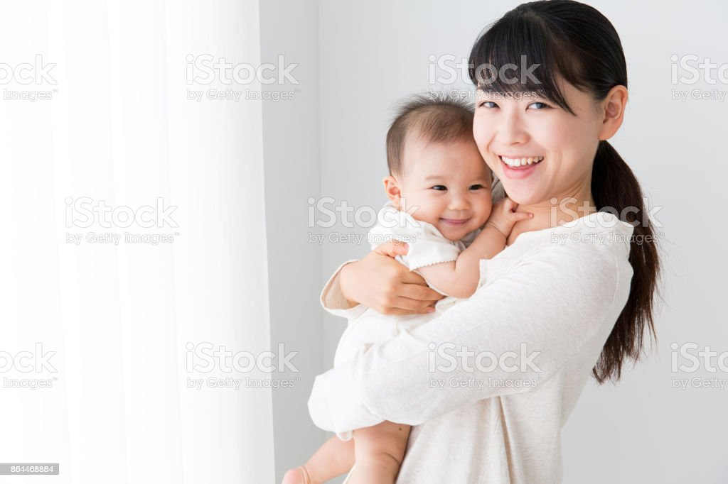 portrait of asian mother and baby in living room stock photo