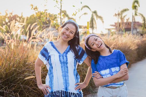 Portrait of Asian mother and daughter in the park, Family relaxing and spending time together at outdoors