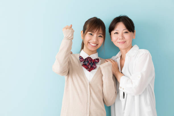 portrait of asian mother and daughter on blue background portrait of asian mother and daughter on blue background japanese school girl stock pictures, royalty-free photos & images
