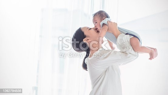 Portrait of asian mother lifting and playing with newborn baby, baby talking to mother. Health care family love together. Asian girl lifestyle. Asia mother's day concept