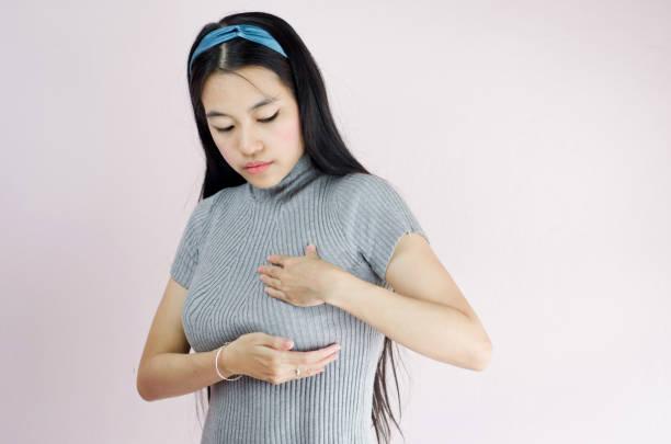 porträt von asiatischen oder thai schöne frau hand überprüfen klumpen auf ihrer brust auf anzeichen von brustkrebs auf krepp rosa hintergrund, gesunden lebensstil-konzept - symptome brustkrebs stock-fotos und bilder