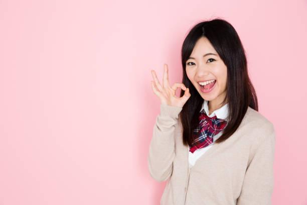 ピンクの背景に分離されたアジア学校の女の子の肖像画 ストックフォト
