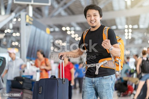 842907838 istock photo Portrait of Asian traveler with luggage with passport standing over the flight board for check-in at the flight information screen in modern an airport, travel and transportation with technology concept. 1050216860