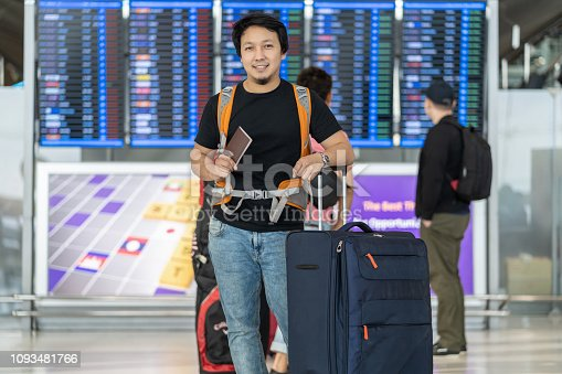 842907838 istock photo Portrait of Asian traveler with luggage with passport standing over the flight board for check-in at the flight information screen in modern an airport, travel and transportation with technology concept. 1093481766