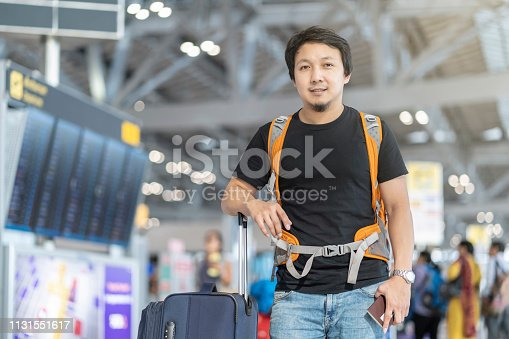 Portrait of Asian traveler with luggage with passport standing over the flight board for check-in at the flight information screen in modern an airport, travel and transportation with technology concept.