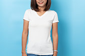 istock Portrait of asian woman in a blank white T-shirt on blue background Mock-up 1126380678