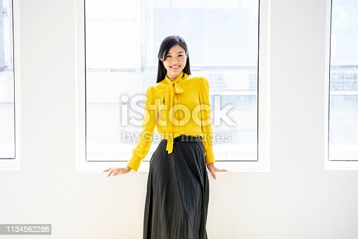 Attractive Chinese woman standing by window, wearing yellow blouse and black skirt, looking at camera, smiling, cheerful, confidence