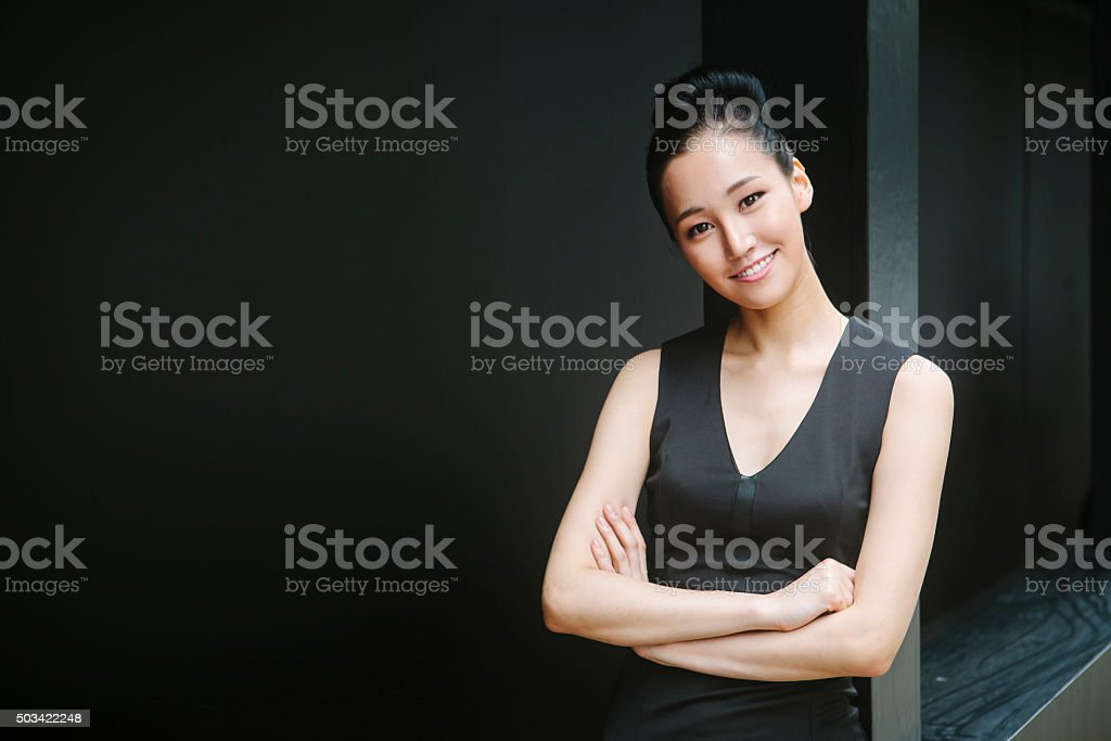 Portrait of Asian Woman Portrait of beautiful asian businesswoman looking at camera and smiling. Dark background. 20-29 Years Stock Photo