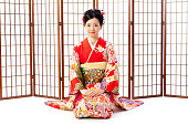 白い背景があるに分離された振袖を着ているアジアの女性の肖像画