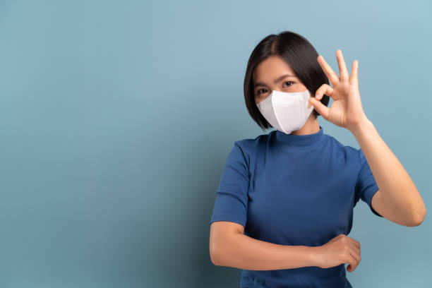 Portrait of asian woman wearing the hygienic mask isolated on blue background stock photo