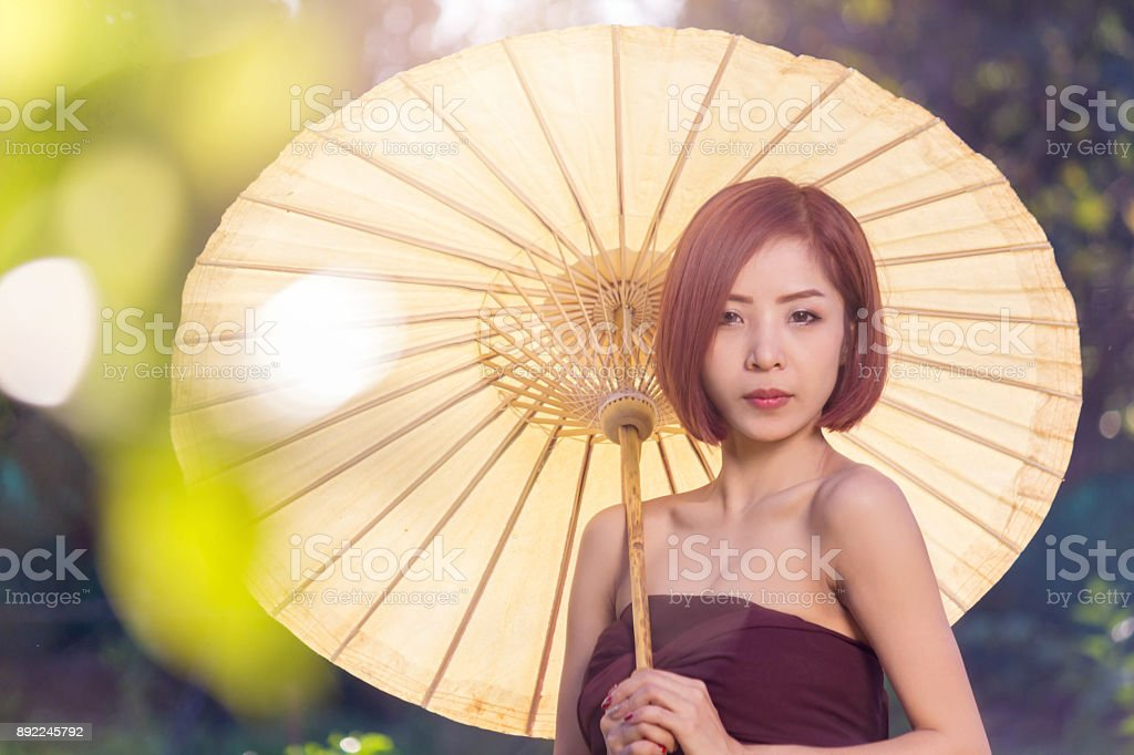 Portrait of asian woman wearing traditional thai holding of yellow umbrella, beautiful thai woman in thai costume, beautiful asian woman stock photo