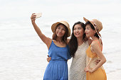 portrait of asian young beautiful woman wearing long dress standing on sea beach taking a photography by smart phone ,selfie in popular activities of people modern lifestyle