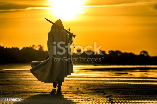 Portrait of assassin in white costume with the sword at the sea. Sunset time. Beautiful orange colors. Silhouette of man.