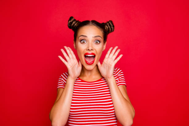 wow! portrait of astonished surprised girl with wide open mouth eyes gesturing with palms near face isolated on red background - smile woman open mouth foto e immagini stock
