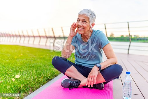 497687118 istock photo Portrait of athletic mature woman resting after jogging outdoors at park 1254526690