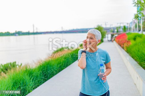 497687118 istock photo Portrait of athletic mature woman resting after jogging. 1161831695