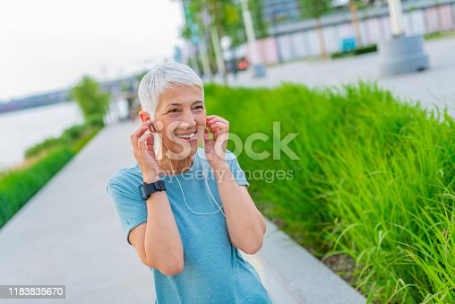 497687118istockphoto Portrait of athletic mature woman resting after jogging. 1183835670