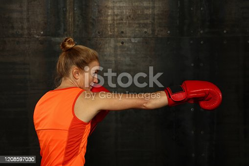 497607484 istock photo Portrait of athletic woman in boxing stance 1208597030