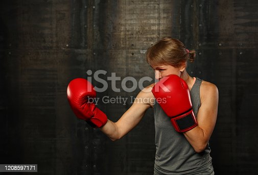497607484 istock photo Portrait of athletic woman in red boxing gloves 1208597171