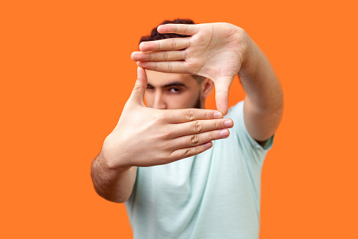 Portrait of attentive curious brunette man in casual white t-shirt looking at camera with one eye, focusing through photo frame made of fingers. indoor studio shot isolated on orange background