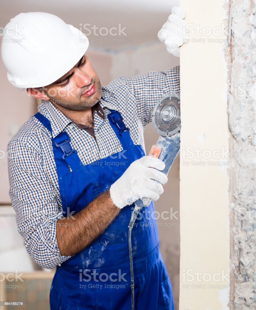 Portrait of attentive repairer man standing with electric saw indoors royalty-free stock photo