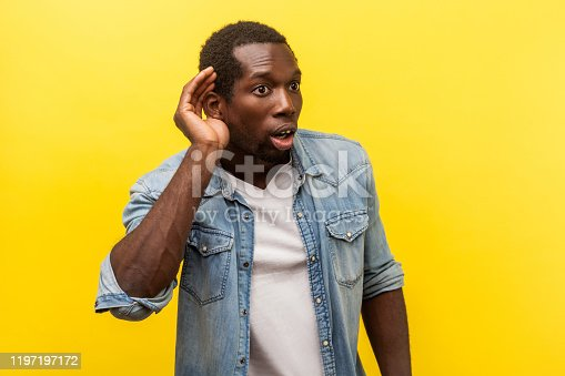 Portrait of attentive surprised man in denim casual shirt with rolled up sleeves putting hand to ear to hear better, listening carefully to rumors. indoor studio shot isolated on yellow background