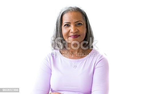 Beautiful African American senior woman in a pink shirt smiles cheerfully at the camera.