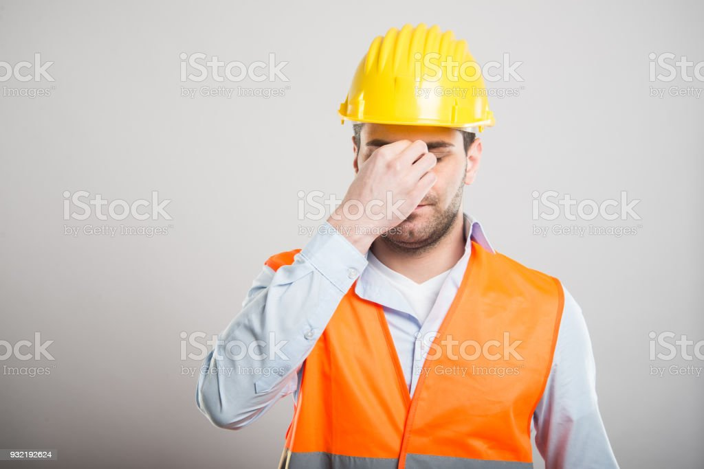 Portrait of attractive architect making tired gesture on gray...