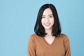 青の背景に分離された魅力的なアジアの女性の肖像画