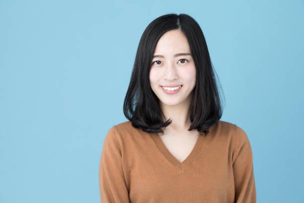 藍色背景下的迷人亞裔女性肖像 - 日本人 個照片及圖片檔
