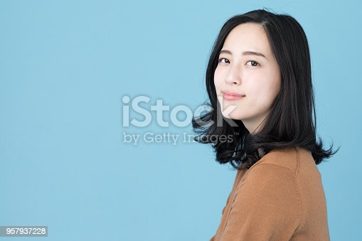 istock portrait of attractive asian woman isolated on blue background 957937228