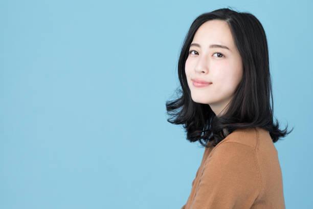 藍色背景下的迷人亞裔女性肖像 - 僅年輕女人 個照片及圖片檔
