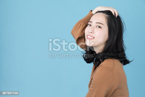istock portrait of attractive asian woman isolated on blue background 957937240