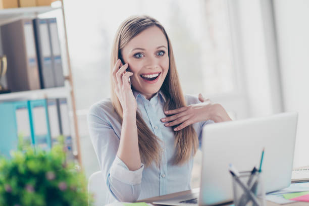 portrait of attractive, astonished, glad, cheerful girl with open mouth in shirt having conversation on smart phone with surprised expression, sitting in workstation, workplace at desk - smile woman open mouth foto e immagini stock