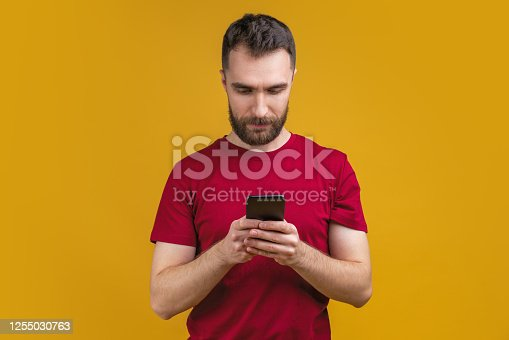 1032204252 istock photo Portrait of attractive bearded man reading message on his mobile phone isolated over yellow background 1255030763