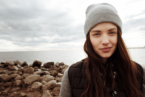 Portrait of attractive brunette girl in warm clothes standing on rocky seacoast on cloudy afternoon and smiling at camera