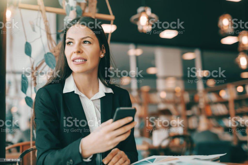 Portrait of attractive businesswoman in formal wear using smart phone...
