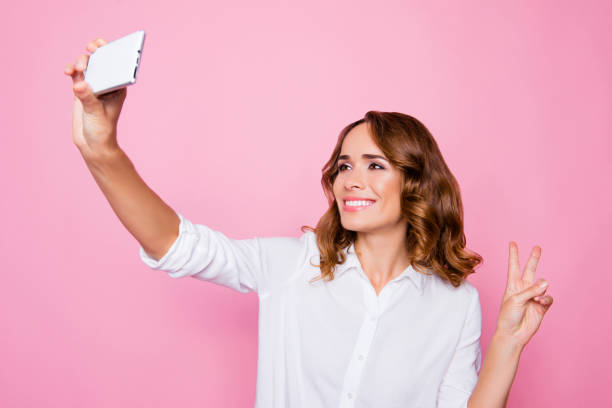 Portrait of attractive charming smiling woman taking a selfie on her smartphone and showing v-sign, isolated on bright pink background stock photo