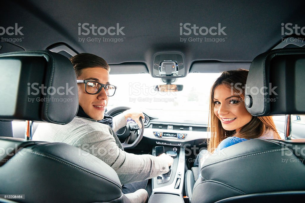 Portrait of attractive cheerful couple driving luxury car in city stock photo